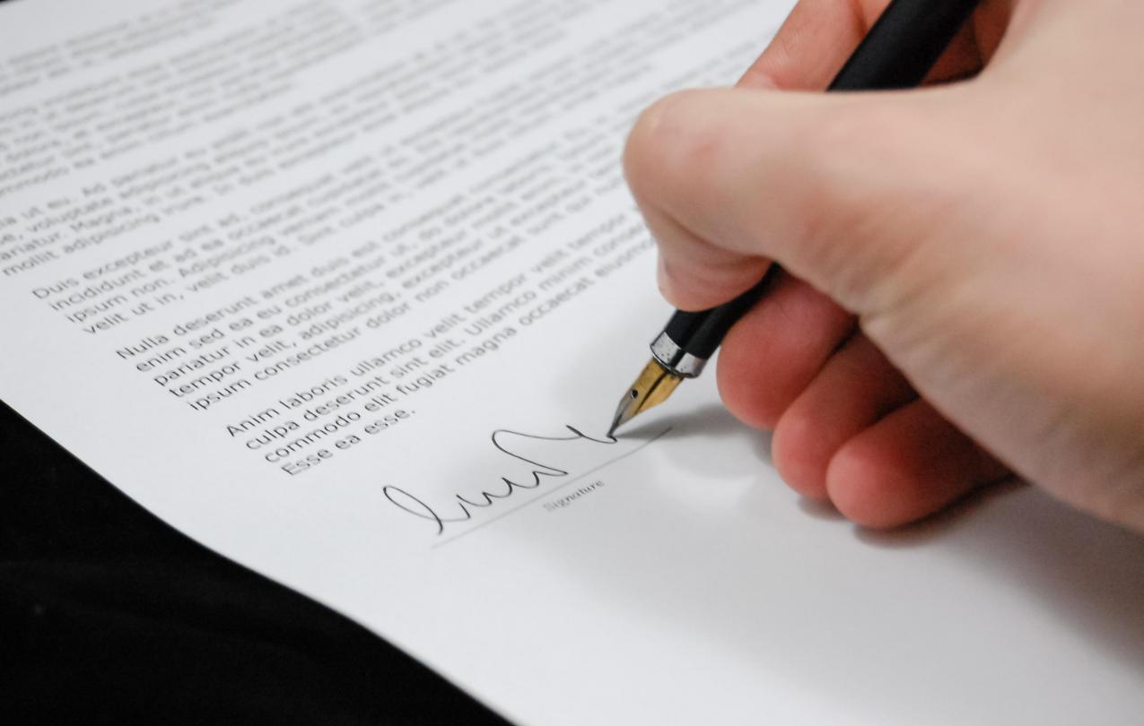 Person signing a piece of paper, used to indicate election certification,  CC0 from pexels.com