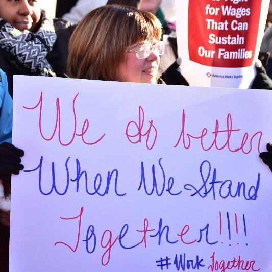 "Woman holding sign that says ""We do better when we stand together"""